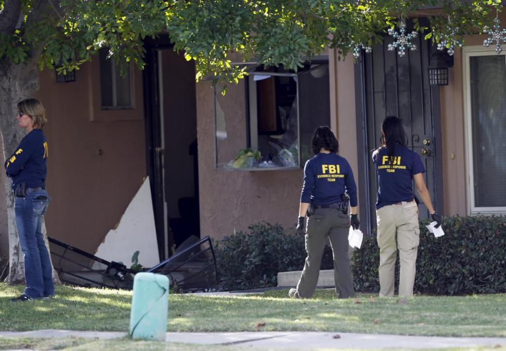 FBI agents search outside the residence that is in connection to the shootings in San Bernardino, California